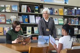 Photo of librarian Russ Iwami with students perusing books